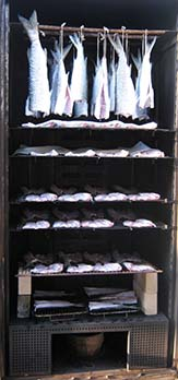 Wet fish are drying until they feel dry or at least tacky to touch. No smoke is applied yet.