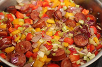 Chopped onions, bell pepper and celery is added and briefly pan-fried